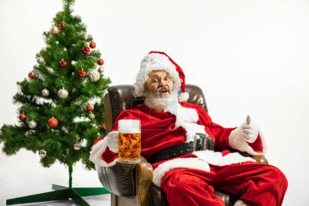 Photo for Santa Claus drinking beer near the Christmas tree, congratulating, looks drunk and happy. Caucasian male model in traditional costume. New Year 2020, gifts, holidays, winter mood. Copyspace for your - Royalty Free Image