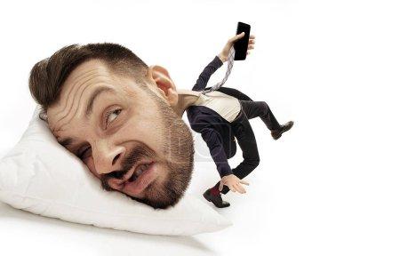Photo pour Appel manquant et messeges. Grande tête sur un petit corps allongé sur l'oreiller. L'homme ne peut pas se réveiller et marcher pour aller au travail cause des maux de tête et un sommeil excessif. Concept d'entreprise, de travail, de hâte, de délais . - image libre de droit