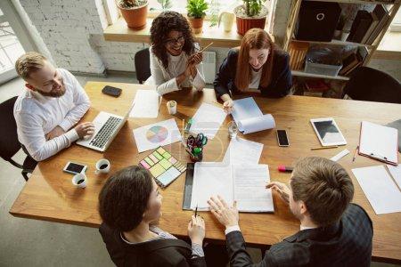 Photo pour Vue de dessus. Groupe de jeunes professionnels des affaires en réunion. Divers groupes de collègues discutent de nouvelles décisions, plans, résultats, stratégie. Créativité, lieu de travail, entreprise, finance, travail d'équipe . - image libre de droit