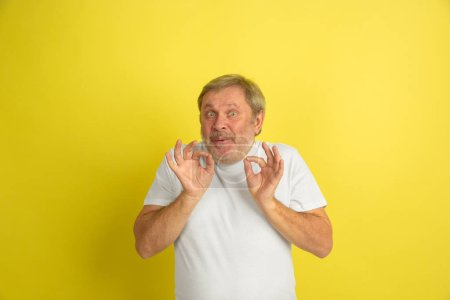 Photo pour Salutation, geste d'invitation. Portrait d'un homme de race blanche isolé sur fond de studio jaune. Belle mannequin masculin en chemise blanche posant. Concept des émotions humaines, expression du visage, ventes, publicité. Copyspace. - image libre de droit