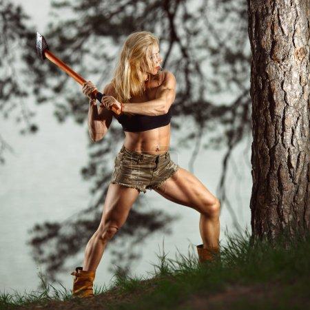 Foto de Mujer muscular cortando un árbol. Leñador de fitness mujer - Imagen libre de derechos