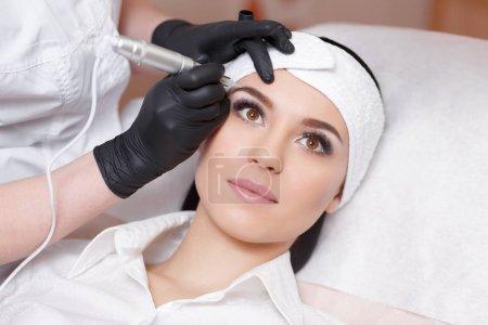 Photo pour Un maquillage permanent. Tatouage permanent des sourcils. Cosmetologue appliquant un maquillage permanent sur les sourcils tatouage des sourcils - image libre de droit