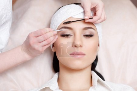 Beautiful young woman gets eyebrow correction procedure