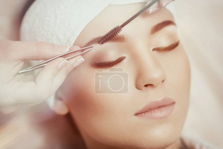 Photo for Permanent makeup. Beautiful young woman gets eyebrow correction procedure. Young woman tweezing her eyebrows in beauty saloon. Young woman plucking eyebrows with tweezers close up - Royalty Free Image