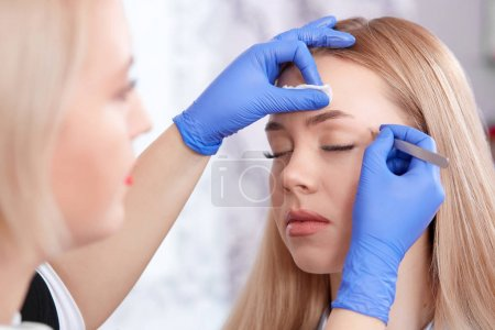 Cosmetologist in gloves plucking eyebrows fol woman.