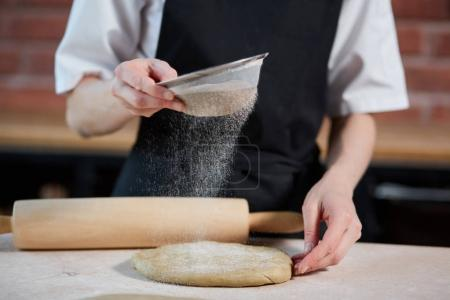 Photo for Horizontal indoors crop shot of cook adding flour to the knead on a kitchen of restaurant. Unrecognizable cook making dough. Making dough - Royalty Free Image