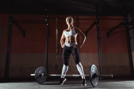 Young fitness girl is standing in the crossfit gym