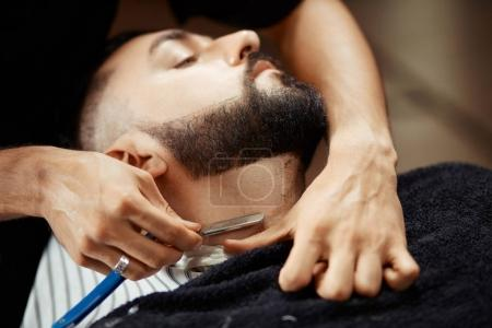 Anonymous man shaving client