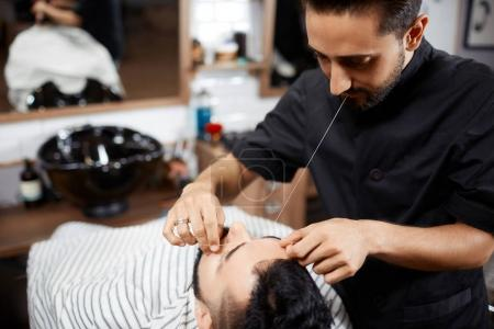 Hairdresser in black cutting bread for brunet man with thread.