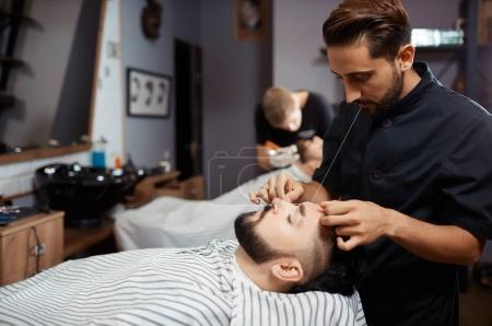 Brunet man visiting barbershop for  cutting beard of thread.