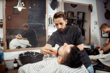 Hairstylist in black combing out bread for brunet at barbershop.