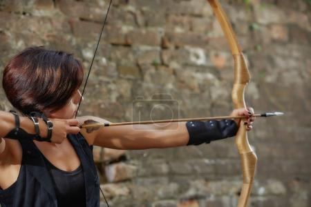 Confident woman shooting from bow, tacking focus, looking away.