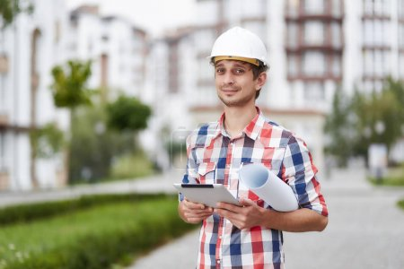 Young architect in front of apartment building