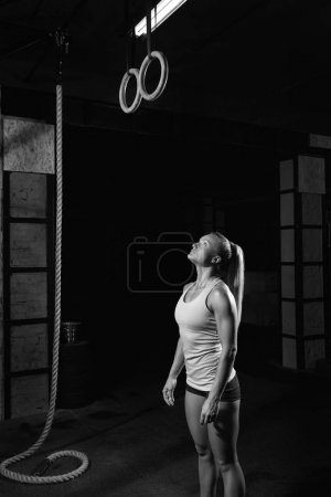 Photo for Vertical shot of a woman preparing to exercise on gymnastic rings during her workout thoughtful confident goal achieving training workout gymnast athlete active activity WOD - Royalty Free Image