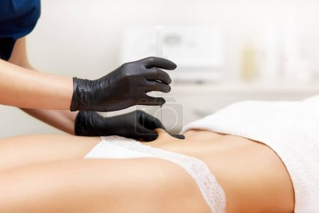Cosmetologist doing lifting and correcting injection in belly.