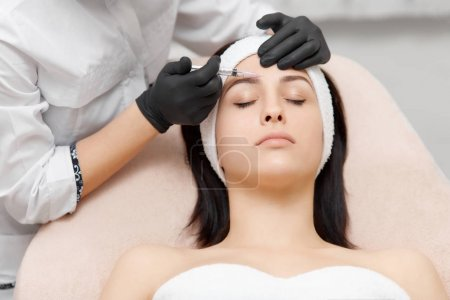 Cosmetology specialist giving lifting injection to beautiful woman.