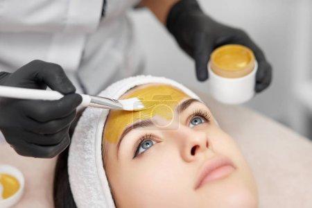 Gorgeous woman enjoying mask procedures in beauty salon.