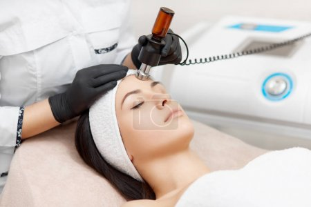 Cosmetology specialist doing radio frequency lifting in beauty salon.