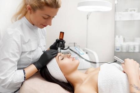 Cosmetologist doing rf lifting in modern beauty salon.