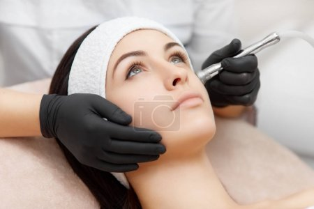 Beautiful woman getting facial procedures of radio frequency lifting.