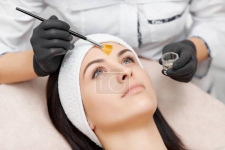 Beautiful woman getting facial peeling mask in beauty salon.
