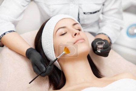Photo pour Belle femme à la peau lisse se détendre et profiter des procédures de spa. Esthéticienne appliquant un masque anti-acné, faisant peler le visage. Concept de visage, rajeunissement et régénération de la peau . - image libre de droit