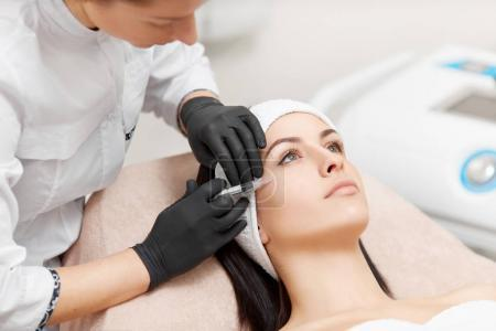 Beautician making anti-wrinkle injection in womans face.