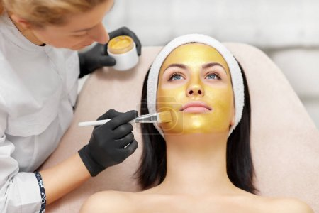 Applying of gold facial mask on skin of beautiful brunette.