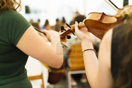 Women playing violins in concert hall