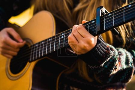 Anonymous person playing guitar while traveling