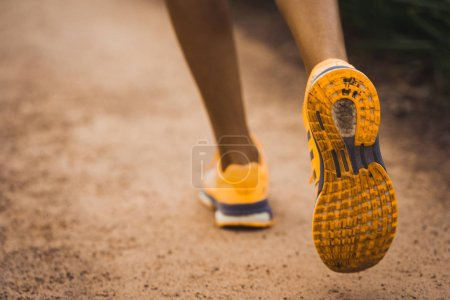 Crop person in sneakers running