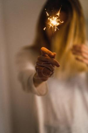Anonymous girl with burning sparkler