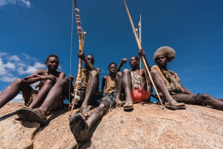 Photo for Stock photo of a group of five African hunters sitting on a rock with bows and arrows in Tanzania - Royalty Free Image