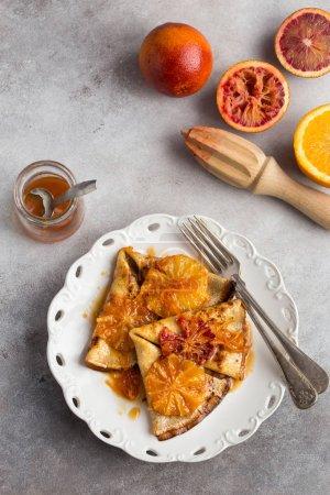 crepes suzette, delicious pancakes with orange sauce, square ima