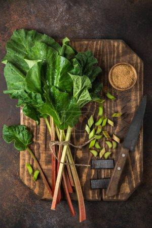 fresh organic rhubarb on wooden cutting board