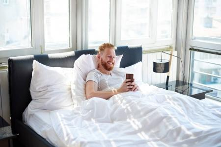Man with phone in bed