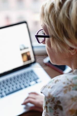 Foto de Vista posterior de la mujer en gafas sentado y trabajando en el ordenador portátil sobre fondo borroso . - Imagen libre de derechos