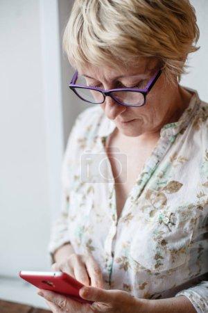 Photo pour Mature confiant femelle dans des lunettes regardant l'écran de smartphone . - image libre de droit