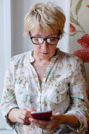 Foto de Vista frontal de la mujer madura en gafas de pie y utilizando el dispositivo . - Imagen libre de derechos