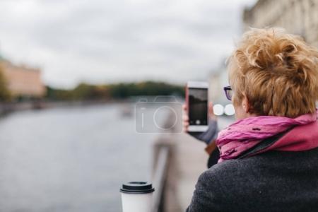 Photo pour Vue arrière de la femme blonde adulte prenant des photos de smartphone de l'esplanade . - image libre de droit