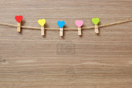 Multicolored decorative clothespins with a heart on a rope.