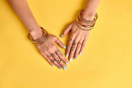 Fasion female manicure with gold bijouterie.