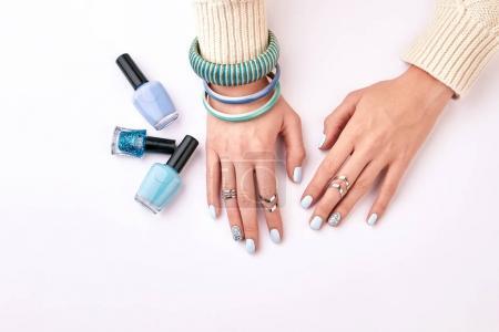 Trandy female manicure with blue bracelets on a white background