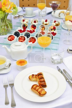 Photo for Table set up for continental breakfast: muesli, fruits and pastry. - Royalty Free Image