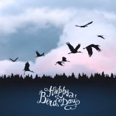 Happy Bird day! Hand written inscription Storks silhouettes on sunset sky
