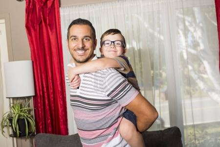 Father and son having fun at home in living room