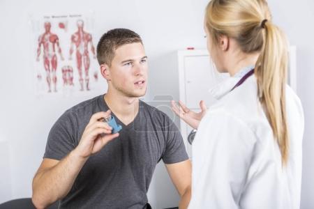 Medical doctor applying oxygen treatment on a sporty men