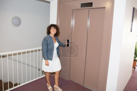 Smiling woman standing and waiting the elevator