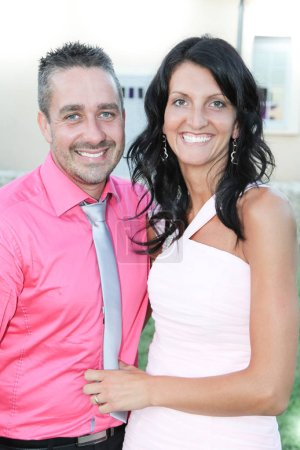 cheerful woman in pink dress with man ready for party
