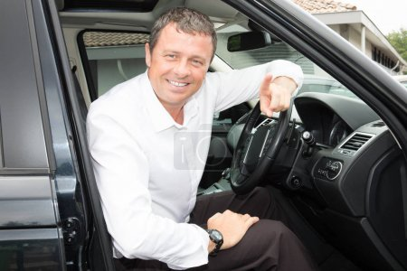 Portrait of an handsome smiling business man elegant driving his car